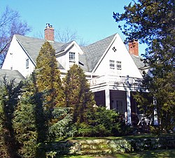 A white house with pointed gray roofs and a front porch behind evergreen trees and shrubs. There is a stone retaining wall in front, at the bottom of the image.