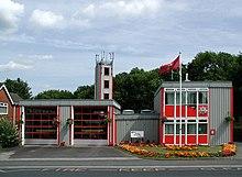 En grå och röd, mycket kantig och ren snygg prefabricerad byggnad med två vikar.