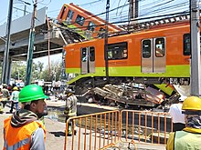 One of the railcars is being lifted by a crane. Behind it, the second railcar still hanging. Below them, a car is seen below the debris.