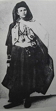 A black and white photograph of a young woman, wearing an assortment of Arabic styled clothing