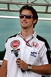 Jenson Button wearing a white T-shirt with sponsors logos and black sunglasses