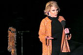 A woman with short blond hair wearing black except for a sparkly orange jacket with earrings. She is holding a microphone, and next to her is a microphone stand with an orange boa hanging from it.