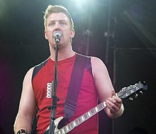 Josh Homme playing guitar onstage