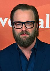 A photograph of a smiling middle-aged Caucasian man with thick beard and combed hair, wearing glasses and a dark blue suit and shirt.