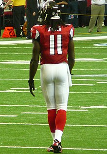 An American football player is in position on the field. He is wearing a red jersey with the number 11 across the back and white pants.