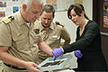 Kate Morrand, right, archeological conservator with the Underwater Archeology Branch, Naval History and Heritage Command, points out the embossing of a two-mast ship on a leather wallet to German navy Capt. Karl 130813-N-CS953-002.jpg