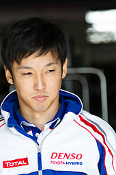 A man in his late 20s wearing a white and blue jacket with sponsors logos on both sides is looking to the extreme left of the camera
