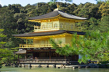 The Golden Pavilion is a building of three storeys with encircling balconies and curving roofs, overlooking a tranquil lake and woods