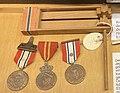 Krigsmedaljer Deltakermedaljen bånd m rosett (9 april 1940 8 mai 1945) Haakon VIIs 70-årsmedalje (Haakon 7 Norges konge) (Norwegian WW2 medals) Skrangle skralle (wooden noise maker matraca) Hjemmefrontmuseet Rakkestad museum Norway.jpg