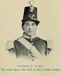A sepia toned portrait photograph depicting the head and shoulders of a young man in an elaborate militia uniform. He wears a tall dress uniform hat.