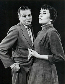middle-aged man with young woman on stage