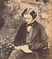 Fotografisk portræt af Charles Lutwidge Dodgson (Lewis Carroll), siddende og holder en bog