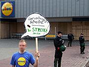 Kritik an den Überwachungsmaßnahmen vor einer verbarrikadierten und polizeigeschützten Filiale am ersten Mai in Kreuzberg