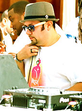 A man wearing a white T-shirt and bowler hat at a mixing table