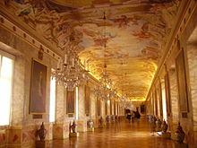 A view down the Ahnengalerie. The walls, made of scagliola, are lined with portraits of the rulers of Württemberg, their arms, and an urn. Above the gallery is a massive fresco, featuring several Classical figures, glorifying the reign of Eberhard Louis.