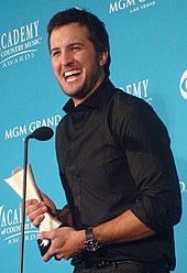 A young man with dark hair wearing a black shirt, speaking into a microphone and holding a trophy