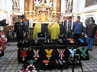 Otto von Habsburg - Otto and Regina lying in repose in the Capuchin Church, Vienna, draped with the Habsburg flag. The insignias of the various orders and decorations accumulated by Habsburg are on display. The guards of honour are dressed in Austro-Hungarian uniforms.