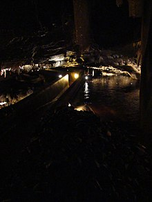 Cave passage with some features lit; within it a concrete pathway sinks to shoulder height with concrete walls either side. Dark brown water runs past outside and just below the top of the walls.