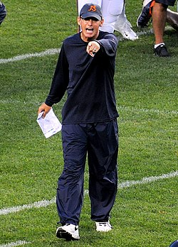 Color photograph of Trestman wearing a dark blue long-sleeve t-shirt, dark blue warmup pants and a blue hat with a Chicago Bears logo pointing with his left hand and holding a sheet of paper in his right hand at his side