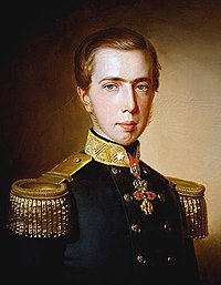 Half-length painted portrait of a young man with thin sideburns who is wearing a double-breasted black military tunic with large gold-braided epaulets and a medal on a ribbon about his neck