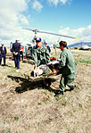 "Members of the 42nd Medical Service Squadron and the 303rd Aerospace Rescue and Recovery Squadron carry a ""victim"" from a crashed TH-1F Iroquois helicopter DF-ST-82-04901.jpg"