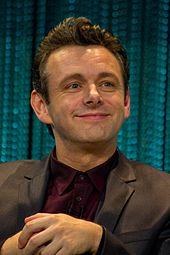 Michael Sheen, a caucasian male in his mid-40s with dark hair, wears a black suit and burgundy shirt.