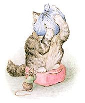 A cat standing on a red cushion with its head wrapped in a blue cloth peeks at a mouse in a green jacket