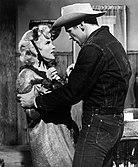 Monroe i Don Murray na przystanku autobusowym.  Ma na sobie obszarpany płaszcz i mały kapelusz zawiązany wstążkami i kłóci się z Murrayem, który ma na sobie dżinsy, dżinsową kurtkę i kowbojski kapelusz.