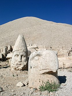 Statues of gods and the pyramid-like tomb-sanctuary of King Antiochus Theos of Commagene rising behind, at the top of Mt. Nemrut