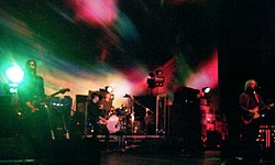 A rock band performing live on stage against a green and red backdrop.