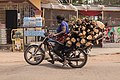 Nigerian Woman transporting wood on her motorcycle.jpg