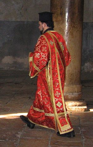 Orarion - Greek Orthodox deacon in the Church of the Nativity in Bethlehem, wearing the double orarion over his sticharion. On his head he wears the clerical kamilavka.