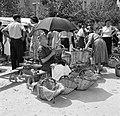 Oudere marktvrouw verkoopt kippen en eieren, zittende onder een paraplu, Bestanddeelnr 254-0767.jpg