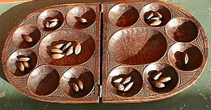 Oware game from Cameroon. On this board players would sit left and right.