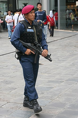 Police Tactical Unit (Singapore) - A PTU officer on patrol at Raffles City during a rehearsal for the National Day Parade 2005. He wore a transitional attire consisting of the new red beret together with the old combat uniform.