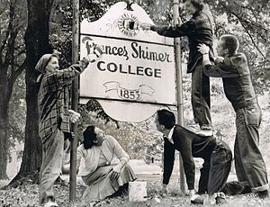 Four-year junior college - Students repainting the Shimer College sign to reflect its change from a four-year junior college to a regular college.