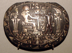 Two Ladies - Image from a ritual Menat necklace, depicting a ritual being performed before a statue of Sekhmet on her throne where she is flanked by the goddess Wadjet as the cobra and the goddess Nekhbet as the griffon vulture, symbols of lower and upper Egypt respectively; the supplicant holds a complete menat and a sistrum for the ritual, circa 870 B.C. (Berlin, Altes Museum, catalogue number 23733)