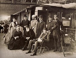 The Empress, Emperor and grandson sit on the promenade deck of an ocean liner, surrounded by their entourage.