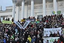 """Mucha gente de pie en los escalones de un gran edificio público sosteniendo pancartas con carteles, como """"Actuar por el clima"""" y """"Go Nuclear""""."""