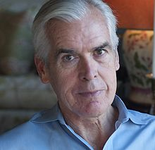 An older white man with a blue collared shirt is looking directly into the camera with a small smile on his face.