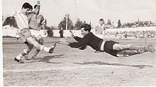 A black-and-white image taken from behind the goal net during a football match. A dark-haired player in a vertically-striped jersey and dark shorts kicks the ball with his right foot while a mustachioed goalkeeper in black dives to stop the shot. Two more players in plain, dark jerseys and white shorts are visible in the background.