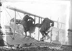 Pilots climbing into the cockpit of a Curtiss JN-4 Canuck. (17428524715).jpg