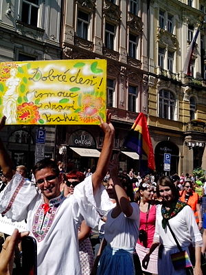 "Czech folklore - A participant of 2013 Prague Pride wearing a traditional Moravian costume (Hanakia) and a sign ""Good day - Olomouc greets Prague"""