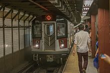 A subway train and many people are seen in New York City's subway system.
