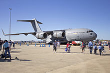 Colour photo of a grey military aircraft on the tarmac of an airport with people in casual clothes walking in front of it