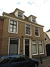 foto van Pand met verdieping en hoog schilddak met topschoorstenen, haaks op de straat