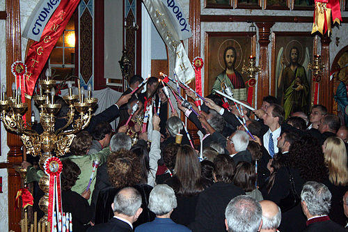 The congregation lighting their candles from the new flame, just as the priest has retrieved it from the altar - note that the picture is flash-illuminated; all electric lighting is off, and only the oil lamps in front of the Iconostasis remain lit. (St. George Greek Orthodox Church, Adelaide). Receiving the Holy Light at Easter.jpg