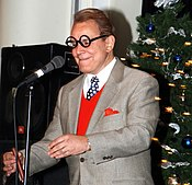 man making impression of George Burns between microphone and Christmas tree