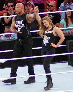 Ronda Rousey - Rousey celebrating with The Rock after forcing Stephanie McMahon and Triple H out of the ring at WrestleMania 31