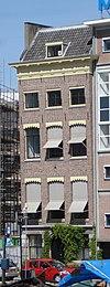 foto van Koopmanshuis, met eenvoudige lijstgevel, waarvan de houten kroonlijst triglyphen en metopen bezit. Hardstenen onderpui, gebosseerd, met getoogd middenvenster, in welks geprofileerde omlijsting een gebeeldhouwde sluitsteen